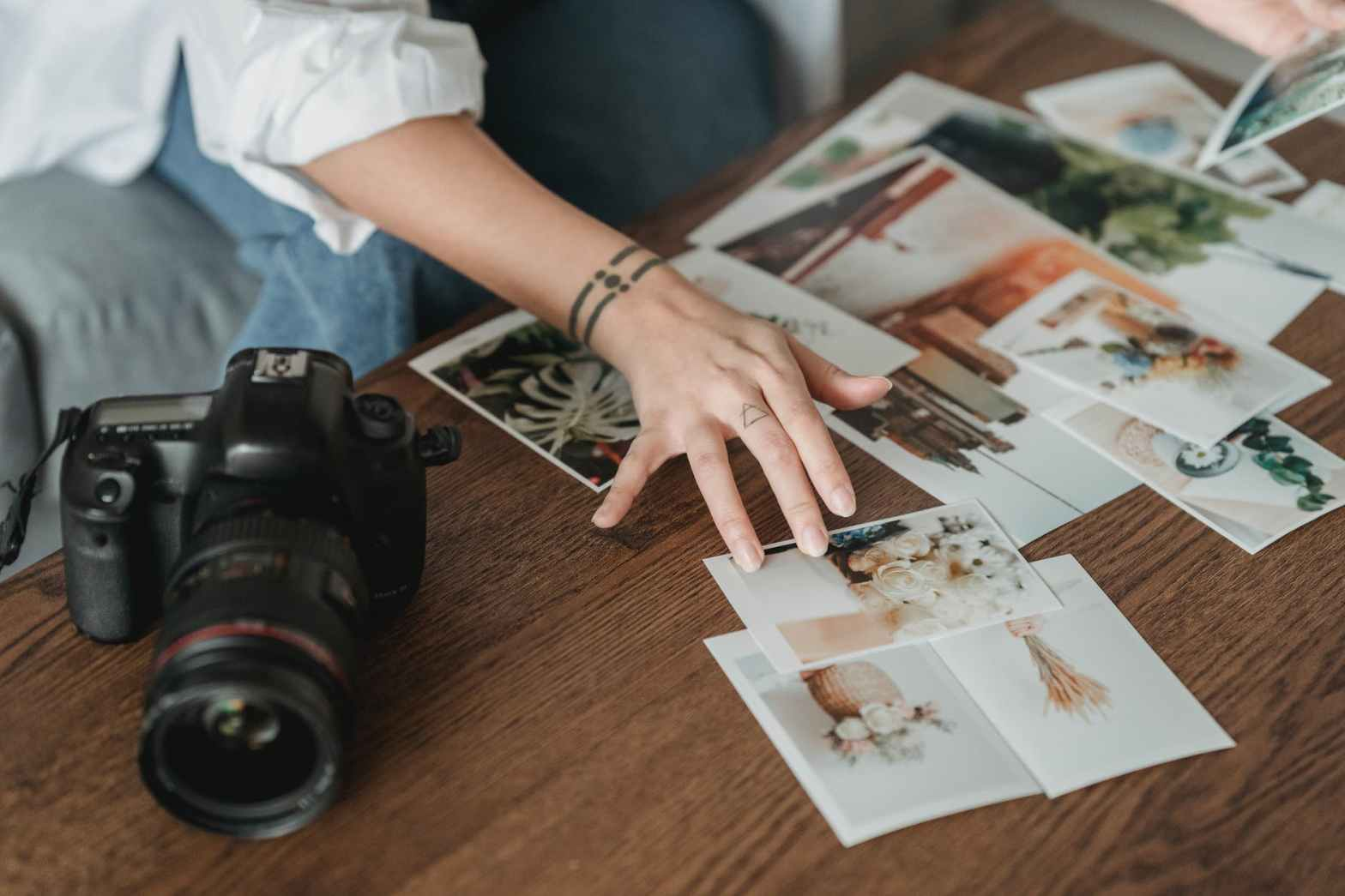 faceless photographer choosing photos at table with digital camera