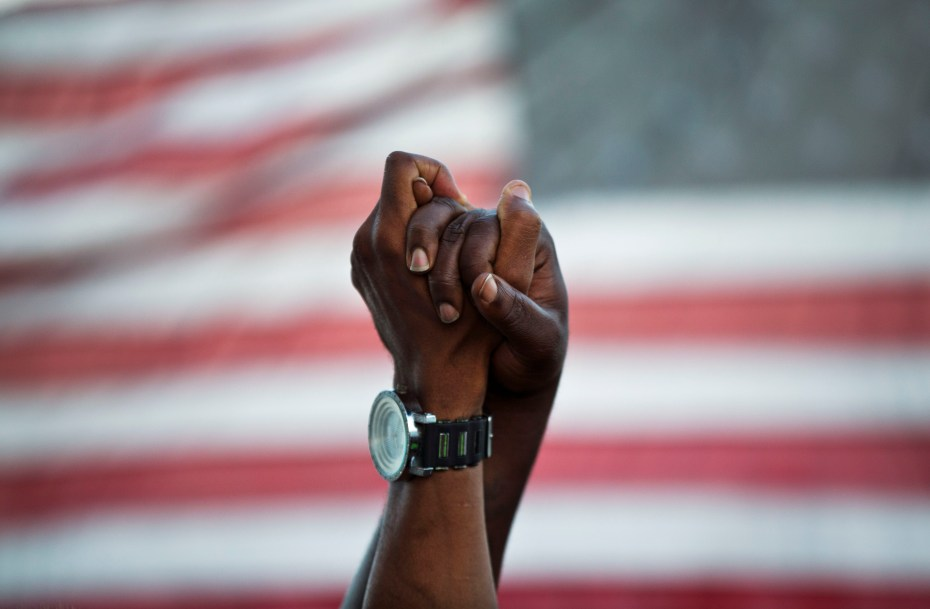 People join hands against the backdrop of an American flag as thousands of marchers meet in the middle of Charleston's main bridge in a show of unity after nine black church parishioners were gunned down during a Bible study, Sunday, June 21, 2015, in Charleston, S.C. (AP Photo/David Goldman)