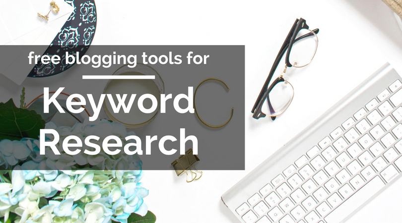 free blogging tools for keyword research text overlaying image of blue flowers, eyeglasses, and keyboard on white background