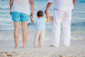 A family of three on a beach in Hawaii.