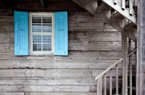 A wooden house with blue shutters.