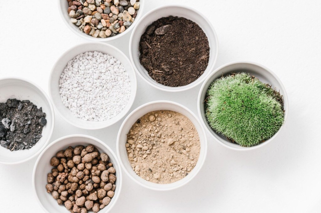 Above view of multiple bowls on a white background containing rocks, perlite, sandy soil, potting soil, and moss