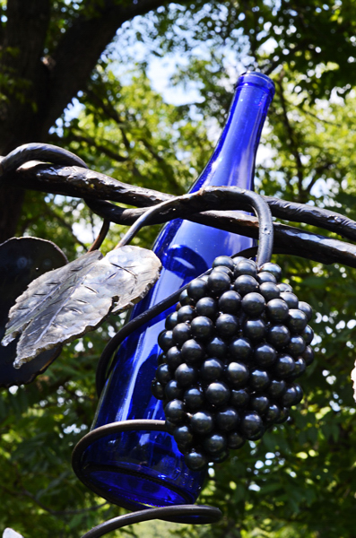 Picture of steel sculpted grapes and leaves against a blue wine bottle, part of a large sculpture by Jim Davis.