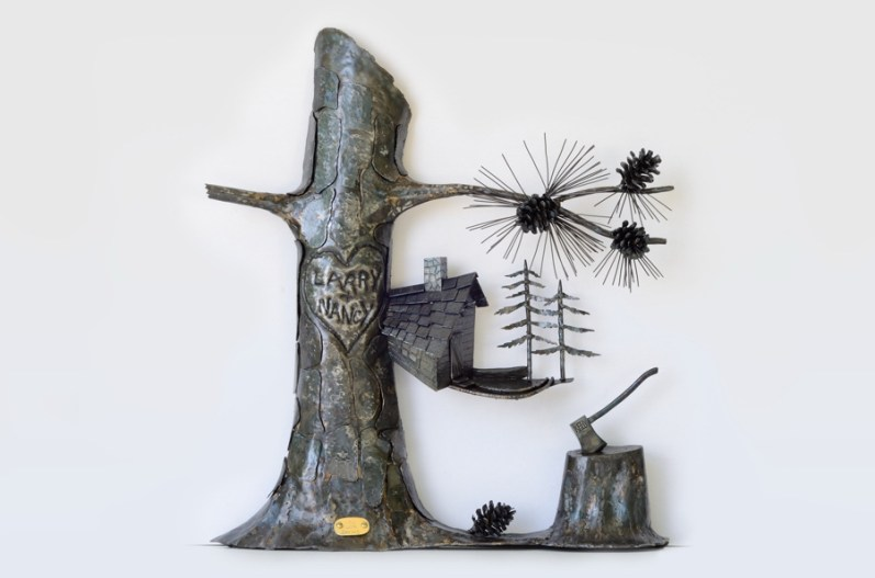 Picture of sculpture of tree with Larry and Nancy carved in a heart, a cabin, pine trees and pine cones, and an axe with the name Kelly embedded in a stump. By Jim Davis