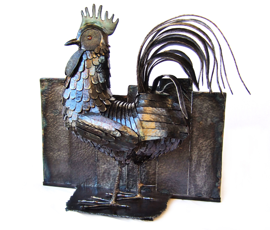 Picture of steel sculpture of a rooster standing against a fence, made by metalworking artist Jim Davis.