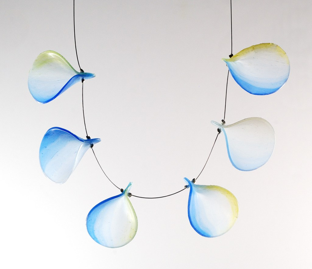 Delicate necklace with flakes of translucent clear plastic arranged on a thin cable. by The Blue Bottle Tree