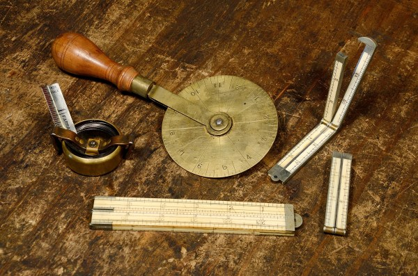 Antique ivory rules, brass traveller, and steel measuring tape.