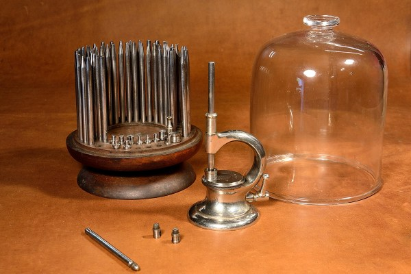 Complete watchmaker's or jeweler's staking tool set, with glass dome.