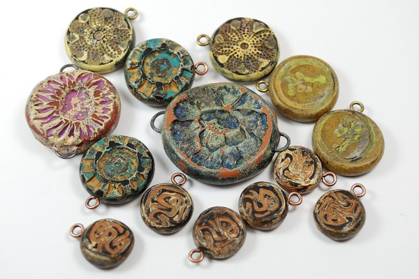 Polymer clay charms and connectors in earth tones by Ginger Davis Allman.