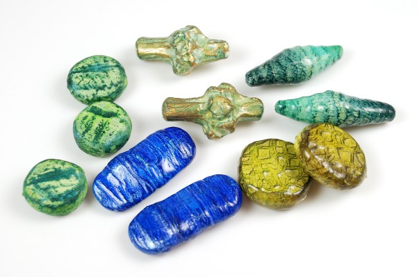 In tones of blue and green, these organic bead shapes are made from polymer clay by Ginger Davis Allman.