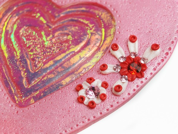 This Holo Heart features crystals embedded into the polymer clay. Learn how to make this bond secure.