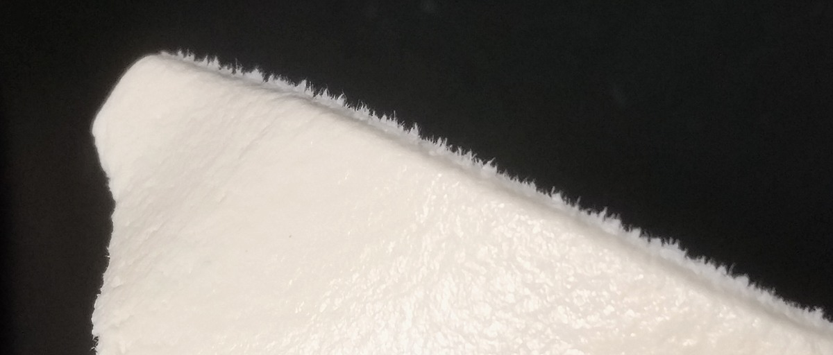The edges of a cut sheet of Fimo Leather have a fuzzy appearance where fibers stick out.