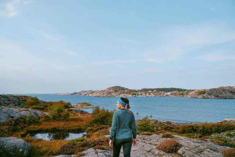 A feature image of a woman in hiking clothes standing on a rocky coastline facing the sea