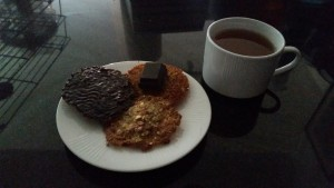 3 cookies plated 1 with chocolate spread, 1 upside down with a chocolate square, 1 right side up no chocolate, and a mug of tea.