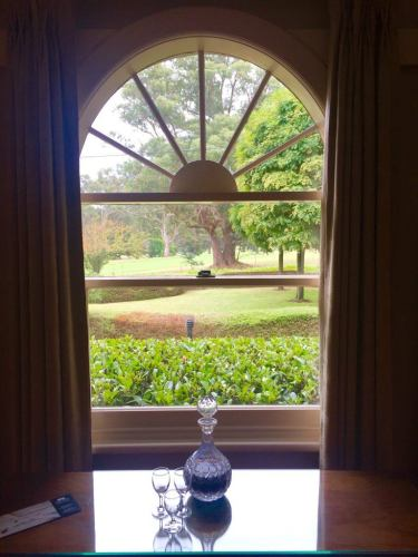 glass bottle of port with glasses in front of a window links house hotel bowral