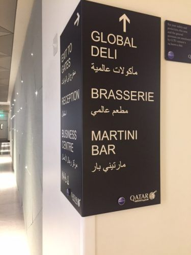 signs for different food and drinks options in qatar airways lounge heathrow