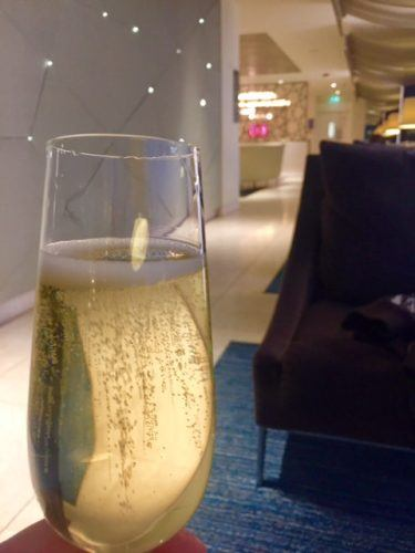 glass of champagne with lounge behind qatar airways lounge heathrow