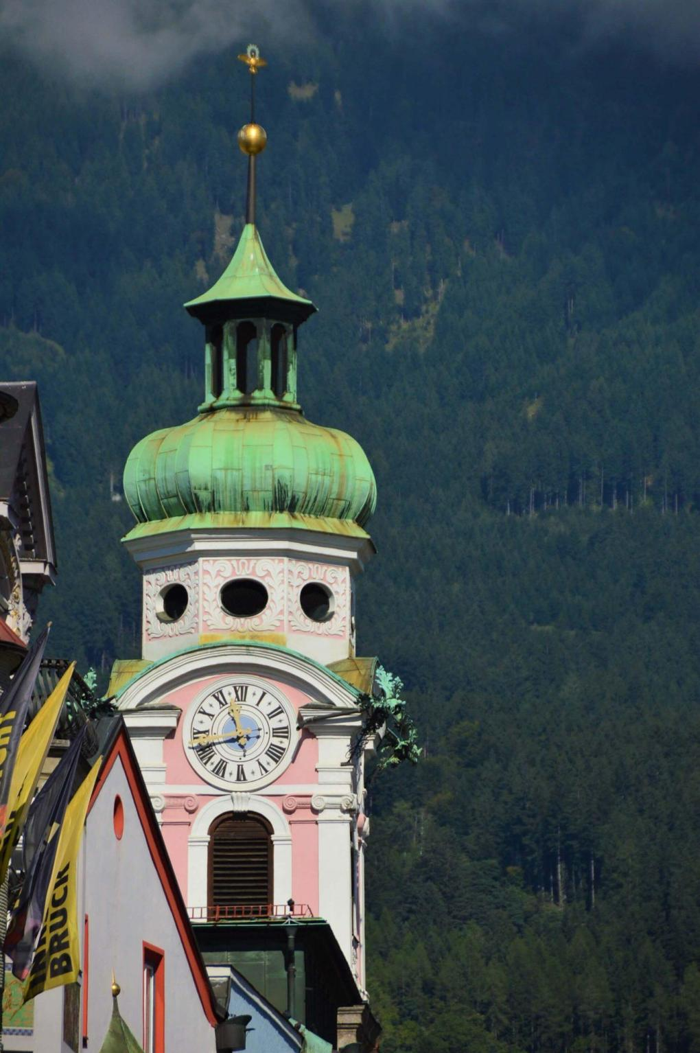 colourful steeple with old fashioned clock and mountains behind innsbruck