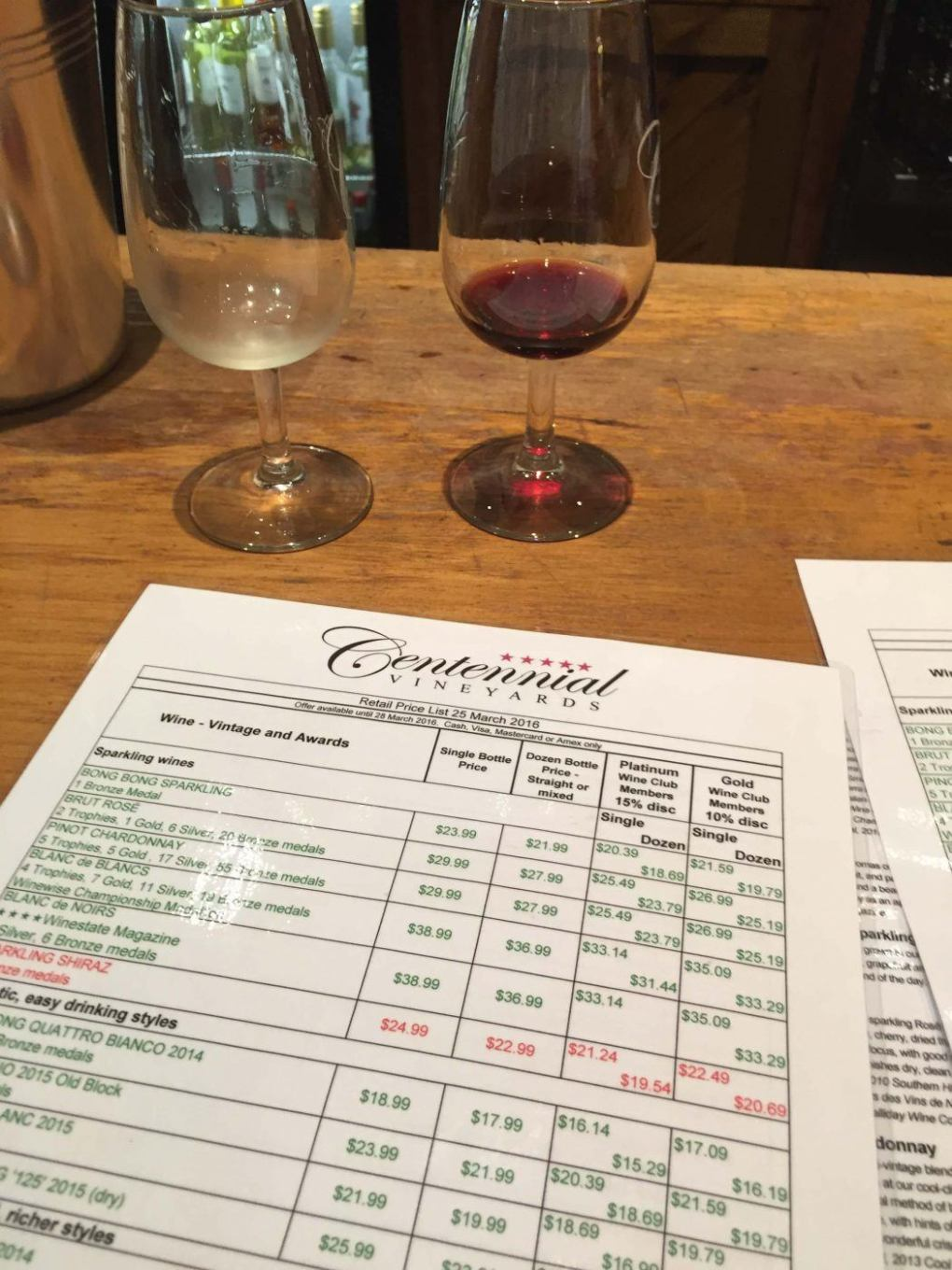 two glasses of wine and a price list at Centennial Vineyards