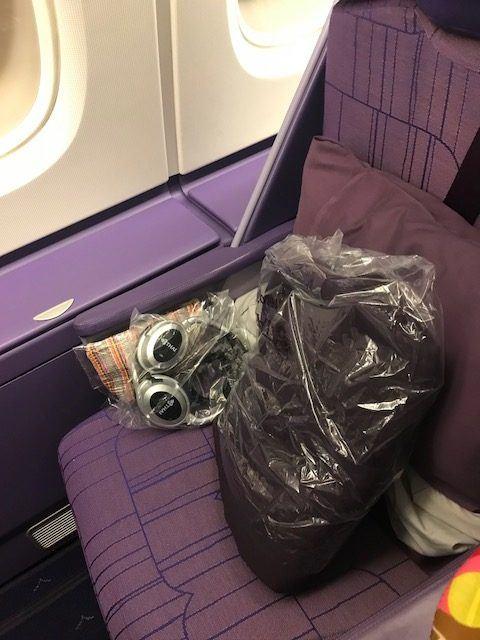 business class bangkok to london seat with pillow and headphones