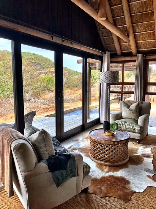 2 armchairs with glass wall and view of outside at kwandwe safari south africa