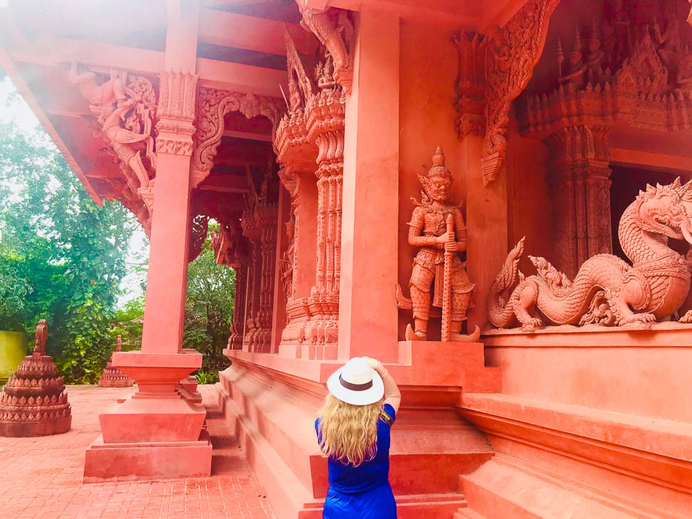woman in hat photographing red temple