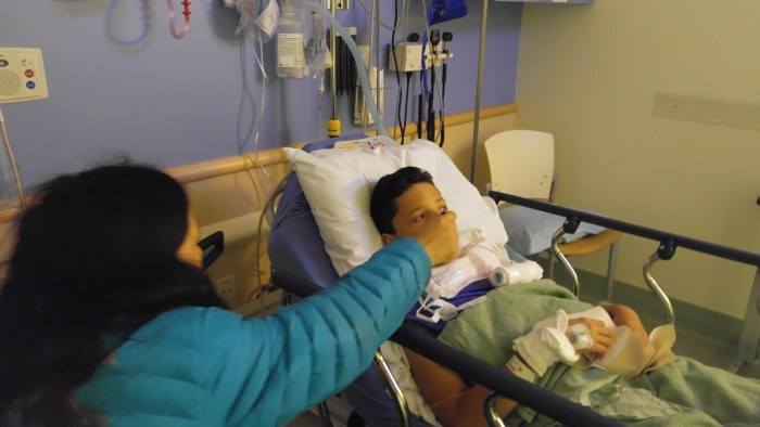 Spoon fed a grape slushy by mom in post-op recovery.