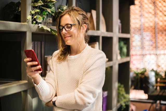 selective focus photography of woman using smartphone beside bookshelf