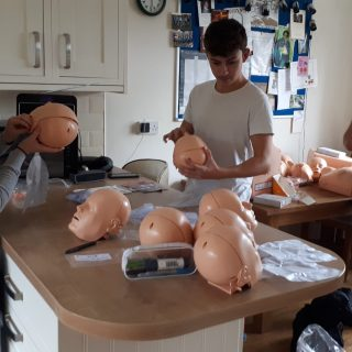 The family bubble help with CPR Manikin assembly and lung changes.