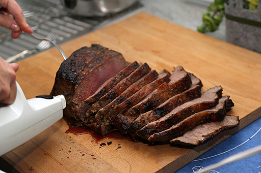 electric carving knife slicing a roast on a wood cutting board