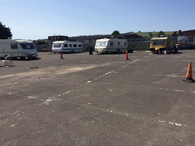 Vehicle dwellers' vehicles at a previous, temporary site. The image shows four vehicles, spread out, in otherwise empty car park.