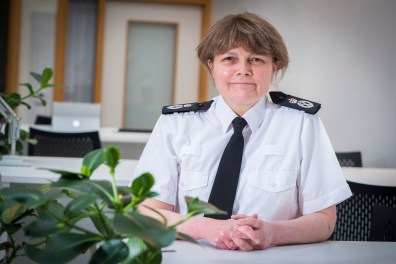 Sarah Crew, Chief Constable of Avon and Somerset Police, sitting. Plants partially obscure the foreground. Her blog focuses on tackling violence against women and girls in Bristol.