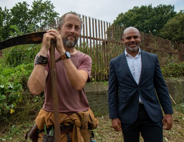 Mayor Marvin Rees at Eastwood Farm in Brislington to launch Bristol's Ecological Emergency Action Plan. Marvin is smiling, alongside a volunteer posing with a scythe.