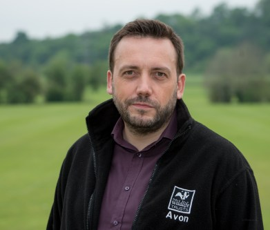 Ian Barrett stands, smiling, in a black fleece with Avon Wildlife Trust's badger logo, with green hills and trees behind him. Ian writes for World Habitat Day.