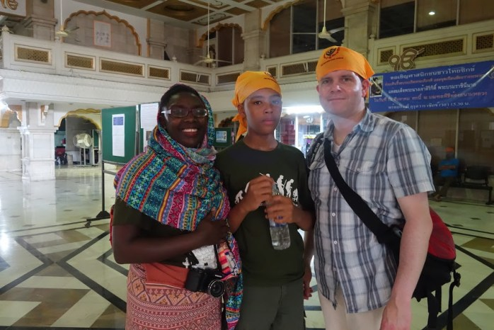 "Myself, ""The Music Producer"", and ""The Tall Young Gentleman"" donning bright yellow scarves and a colourful shawl at the Sikh temple in Bangkok, Thailand."