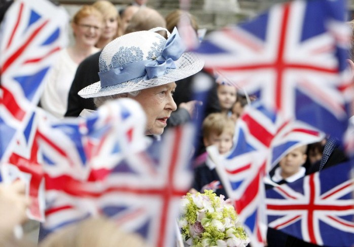 Schoolchildren wave Union flags as the Queen leaves a service of thanksgiving at St Paul's Cathedral to celebrate its 300th anniversary.