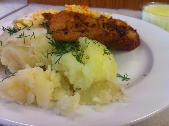 Mashed potatoes sprinkled with dill, breaded fish fillet with coleslaw and a custard pudding at Bar Mleczny Familijny - a mik bar - in Warsaw.