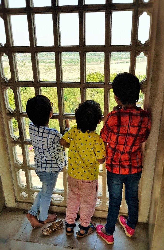 Children looking through a window at the Taj Mahal; Agra; India