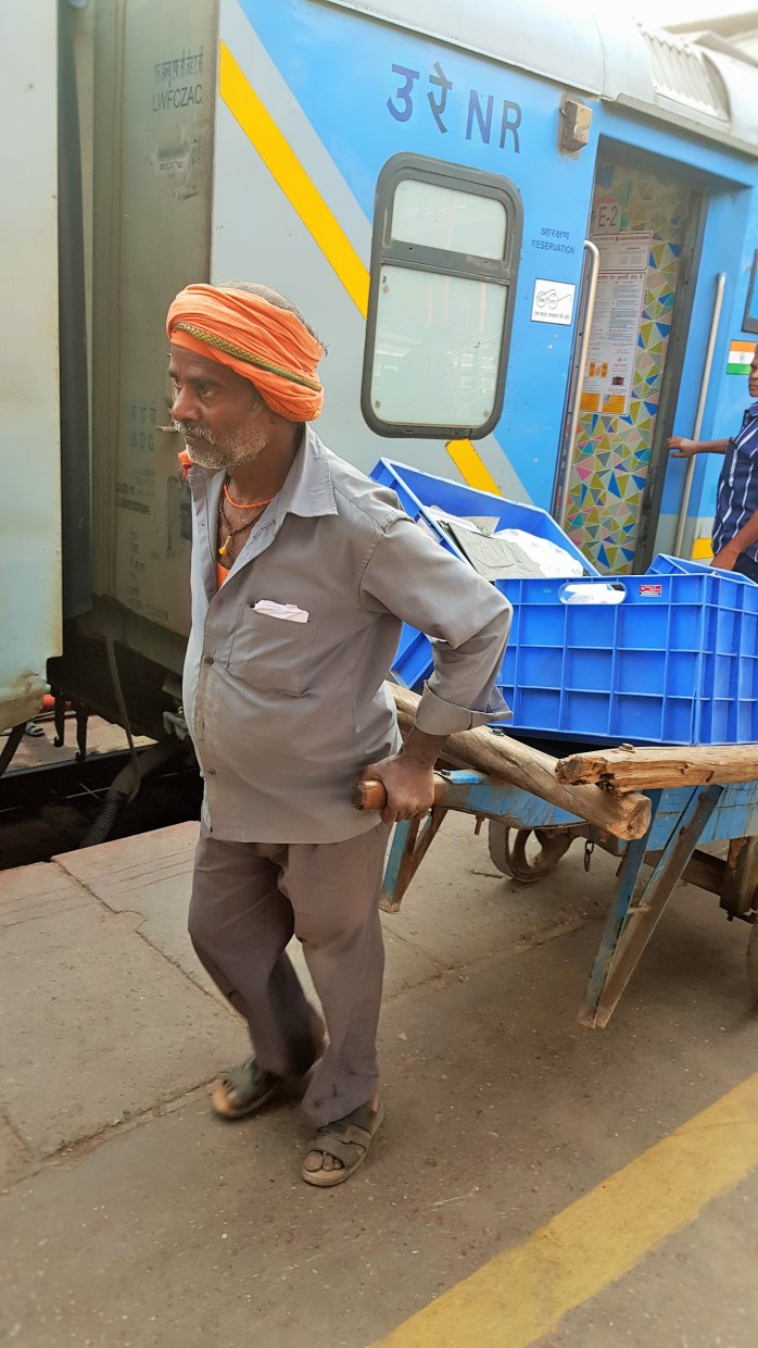 A train porter at Delhi (Hazrat Nizamuddin) train station; train porter; coolie; Indian porter; Indian train porters; porters; Taking the train in India; At the Delhi (Hazrat Nizamuddin) train station; Delhi (Hazrat Nizamuddin) train station; Delhi (Hazrat Nizamuddin); Delhi train station; Hazrat Nizamuddin train station; railway; Indian train; train; trains in India; Indian railway; train station; Delhi; India