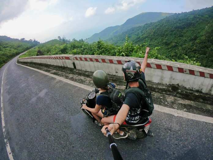 Using selfie stick to take pic while riding motorbike on a pass of Vietnam