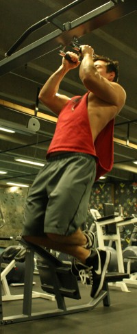 Sergio Felix performs pull-ups using the equipment in Mazama Gym.  Photo by James Miller II | The Broadside.