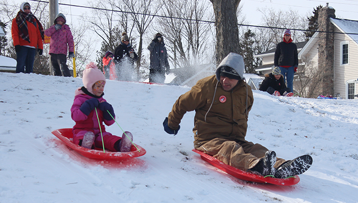 sledding dad and daughter