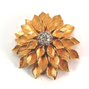 golden flower brooch with rhinestone center