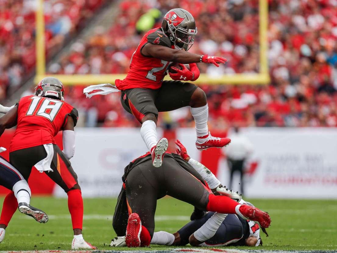 Ronald Jones II jumps over lineman