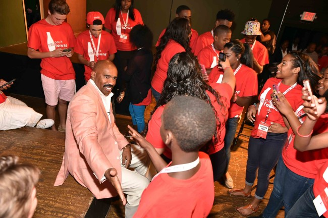 ATLANTA, GA - JULY 25: Comedic legend and media mogul Steve Harvey surprise 2015 Coca-Cola Pay It Forward winners during inaugural Coca-Cola Pay It Forwad Academy at Whole World Improv Theatre on July 25, 2015 in Atlanta, Georgia. (Photo by Moses Robinson/Getty Images for Coca-Cola)