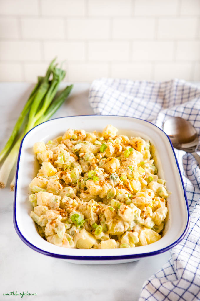 bowl of easy potato salad in white bowl with green onions
