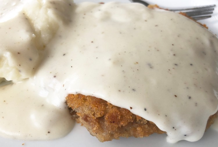 Easy White Country Gravy served over mashed potatoes and country fried steak