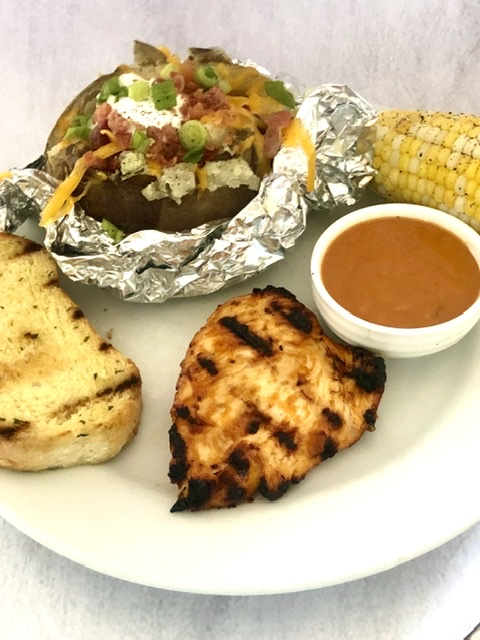 Sweet Baby Ray's Chicken served with garlic bread, corn on the cob and a loaded baked potato