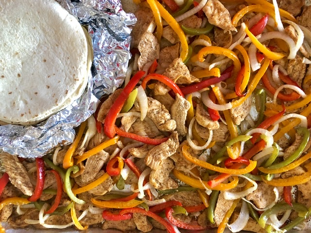 cooked sheet pan chicken fajitas with foil wrapped warm flour tortillas for serving