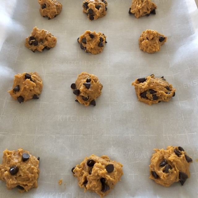 pumpkin chocolate chip cookie dough dropped on baking sheet lined with parchment paper